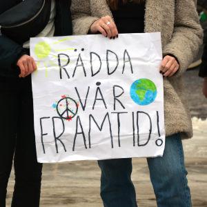 Ett plakat där det står Rädda vår framtid.