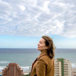 Riitta Havukainen roolissaan Espanjan merimaisemassa. Taustalla meri ja rakennuksia.