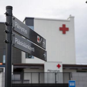 Sairaalan päivystykseen ohjaava tienviitta sairaalan edustalla