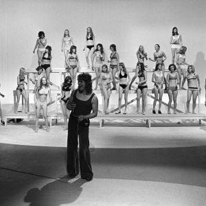 Markku Aro esiintyy 1972. Taustalla bikinipukeisia naisia.
