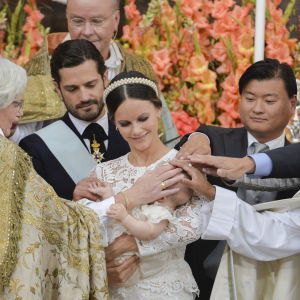 Prinsessan Sofia håller sin son medan arkebiskopen Antje Jackelen, prins Carl Philip, gudföräldrarna Jan-Åke Hansson och Lina Frejd samt hovpastor Michael Bjerkhagen ger den lille sin välsignelse.