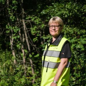 En kvinna står framför en skog i en gul arbetsväst.