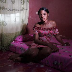 Tummaihoinen nainen istuu paljalla huoneen lattialla