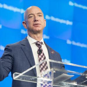Jeff Bezos bakom genomskinlig talarstol med utsträckta händer