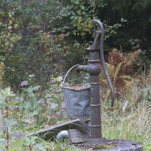 En gammal vattepump med ett plåtämbar som hänger på kranen.