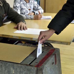 Person lägger röstsedel i låda