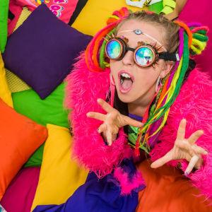 Vicky O'Neon poserar i färgranna kläder med färgade brillor.