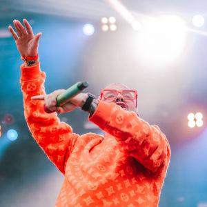 Oranssiin paitaan ja punaisiin aurinkolaseihin pukeutunut J Balvin kädet ilmassa Ruisrockin Niittylavalla. Kuva rajattu vyötäröstä alaspäin.