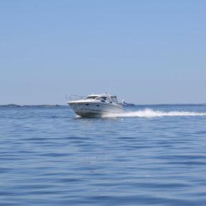 En motorbåt kör på havet i en somrig, spegelblank skärgård.