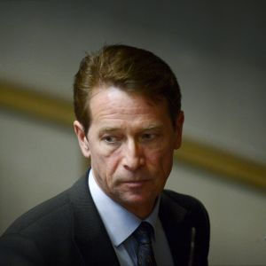 Närbild på Tapani Mäkinen i riksdagen. Han har mörk kostym och tittar neråt med en bister min.