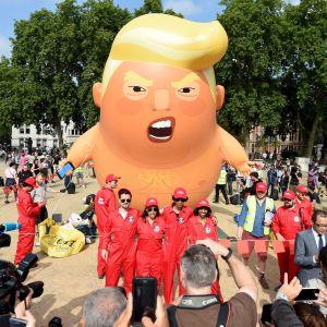 Människor i röda overaller poserar framför en jättelik ballong som föreställer en arg Donald Trump