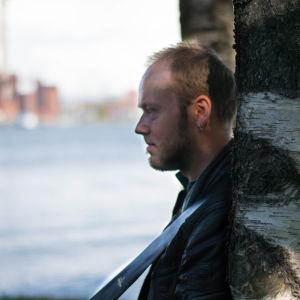 Mikael grönroos i profil lutad mot Björk på Tjärholmen med vatten och fabriker i bakgrunden.