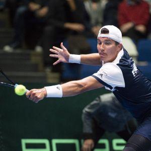 Patrik Niklas-Salminen sträcker sig för att träffa en tennisboll.