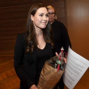 Sanna Marin med blombukett i handen.