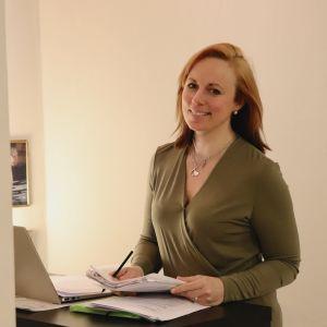 Anna Bertills tittar in i kameran och håller några papper och en penna i händerna.
