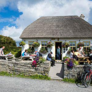 En pittoresk irländsk pub omgärdad av stenmur på landsbygden med folk på terrassen.