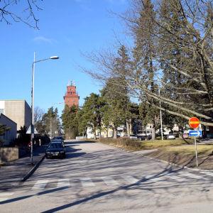 Gata i solsken, några bilar står parkerade på vänstra sidan. I bakgrunden ett rött vattentorn.