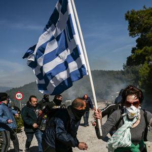 Demonstranter protesterar på ön Lesbos i Grekland. En av demonstranterna håller i en grekisk flagga och de flesta har andningsskydd på sig på grund av polisens tårgas.
