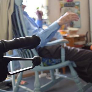 handtaget av en rollator i förgrunden. Harry i sin gungstol i bakgrunden