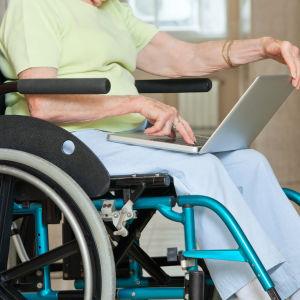En äldre person sitter med bärbar dator i famnen i en rullstol.