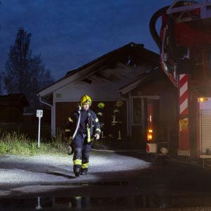 Palomies palosta kärsineen talon edustalla