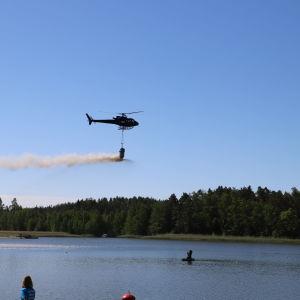 Helikopter sprider ut kalksten i Kolkkaviken i Nådendal.