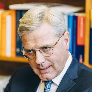 Norbert Röttgen i kostym och glasögon sitter framför en bokhylla.