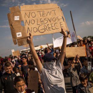 Flyktingar och migranter från det nedbrunna Moria-lägret demonstrerade på fredagen mot planerna på ett nytt läger. Nej till tält, Lesbos och Grekland, står det på ett av plakaten.