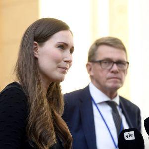 Sanna Marin talar i en usträckt mikrofon, Matti Vanhanen står bredvid.