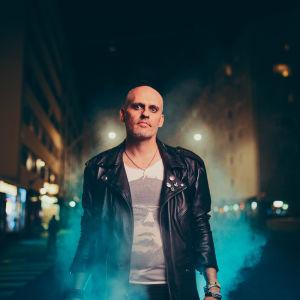 Lasse Grönroos i läderrock på nattlig Vasagata med neonljus och dimma. Promobild för Grönroos Garage.