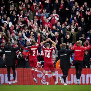 En läktare full av euforiska fans i rödvitt får hälsningar av spelarna efter en match.