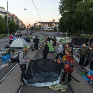 Miljöaktivister slår upp tält på Mannerheimvägen i Helsingfors.