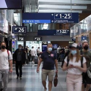 Människor i munskydd går omkring på Helsingfors-Vanda flygplats.
