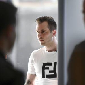Två suddiga figurer framme på bilden, i bakgrunden syns brottsmisstänkta Niko Ranta-aho i en vit t-skjorta med allvarlig min på ansiktet.