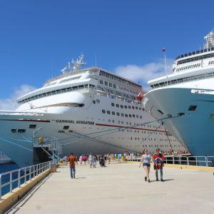 Fören på två kryssningsfartyg som ligger förtöjda intill varandra. På kajen nedanför går människor i solsken.