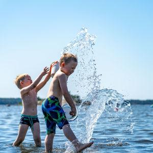 Barn leker i vattenbrynet och stänker vatten på varandra.