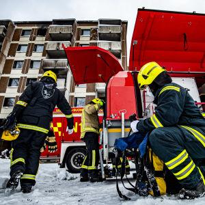 Tre brandmän plockar fram rökdykningsutrustning, brandslangar och munstycken ur brandbilar framför ett höghus, där många fönster och balkonger är svarta av eld och sot.
