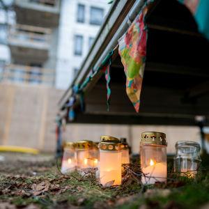 Kynttilöitä Koskelan murhapaikalla. Taustalla rakenteilla oleva kerrostalo.
