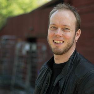 Mikael Grönroos glad på Tjärholmen med röd trävägg och björkar i bakgrunden.