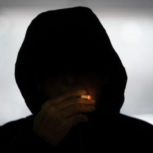 Anonyymi hupparimies polttaa tupakkaa.