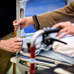 Två händer håller i sjukhsets sänggavel.