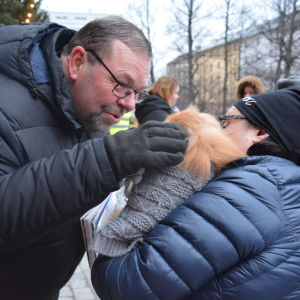Jouni Lehikoinen klappar en liten hund som är i famnen på sin ägare.