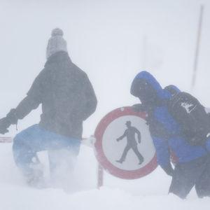 Fotgängare putsar en nedsnöad vägskylt i Arlberg.