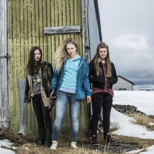 Karaktärerna Jani, Tyra och Renate står vid en grånad utevägg i dramaserien Monster.