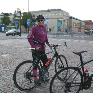Kvinna i cykeloutfit står bredvid sin cykel i Gamla stan i Borgå.