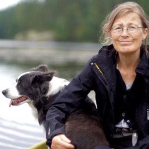 En äldre kvinna sitter i en båt med en bordercolliehund.