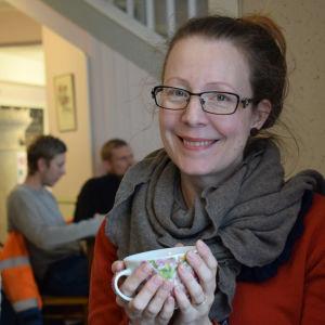 Stina Liman sitter på ett cafe i en röd tröja, ler mot kameran och dricker te.