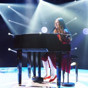 Tinja Höglund på scenen bakom en svart flygel.