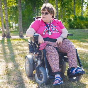 En kvinna i en rullstol på en gräsmatta. Vädret är soligt. Kvinnan tittar bort från kameran och ser allvarsam ut.