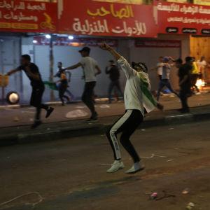 Palestinska demonstranter kastar stenar mot israelisk polis i Nablus på Västbanken.